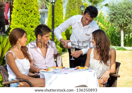 Waiter pouring wine for three young attractive friends seated at an outdoor table in the garden of a restaurant - stock photo