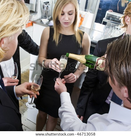 Waiter, refilling champagne glasses from the bottle in a bar on New years eve - stock photo