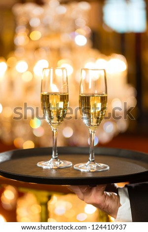 Waiter served champagne glasses on a tray in a fine dining restaurant, a large chandelier is in Background - stock photo