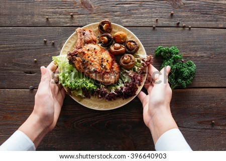 Waiter serving a chicken dish with lettuce and mushrooms. Chief decorating food for presentation in small cafe. Waiter presenting grilled chicken with salad for retail.  - stock photo