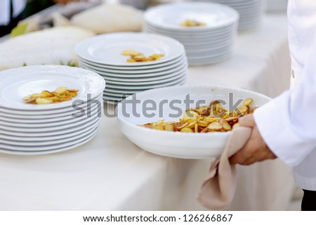 Waiter serving a large bowl of tasty fried potatoes - stock photo