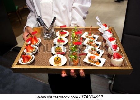 Waiter serving canape selection on slate platter - stock photo