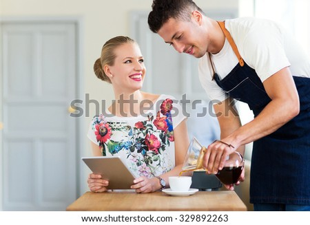 Waiter serving customer at the coffee shop  - stock photo