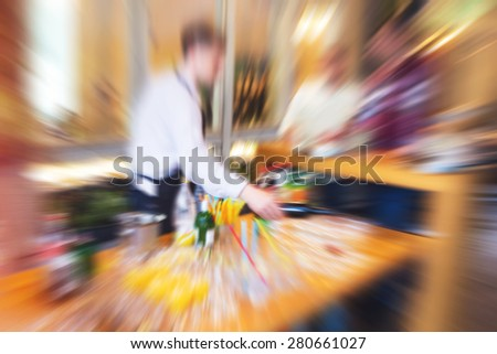 Waiter serving drinks on a tray during wedding evening, defocused with radial zoom blur, vintage retro instagram effect added - stock photo