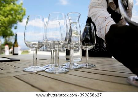 Waiter serving glasses for wine tasting. - stock photo