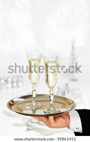 Waiter serving two glasses of champagne to dining table decorated for Christmas - stock photo