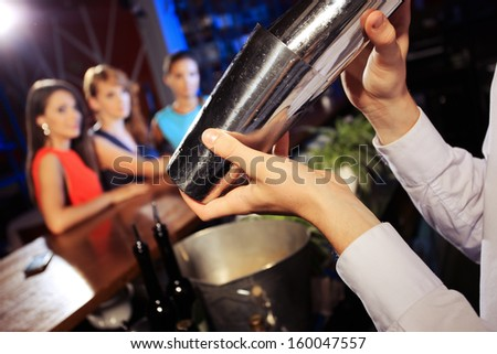 Waiter shaking a cocktail, young women on the background - stock photo