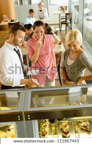 Waiter showing women cakes on window display cafe smiling friends - stock photo