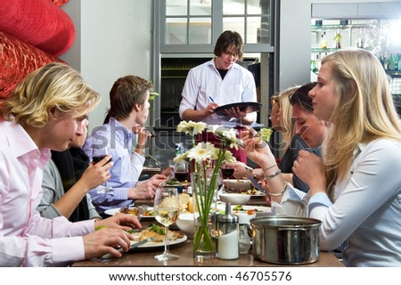 Waiter taking orders from a group of dinner guests at a restaurant - stock photo