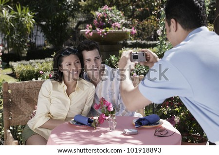Waiter taking photograph of couple at table - stock photo