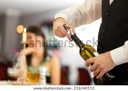 Waiter uncorking a wine bottle in a restaurant - stock photo
