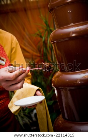 waiter with a strawberry and a chocolate fountain - stock photo
