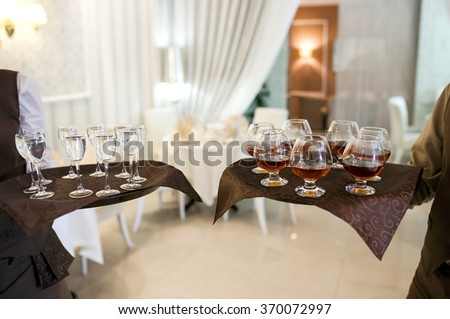 waiter with a tray welcomes visitors - stock photo