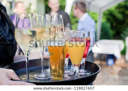 Waiter with dish of champagne, cocktails, beer and juice glasses - stock photo