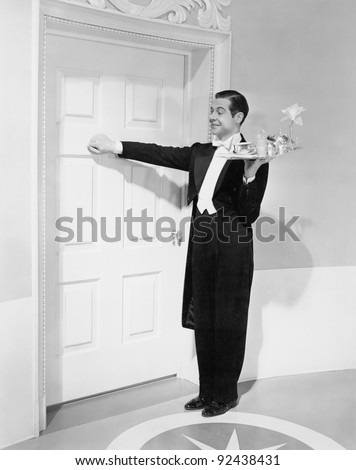 Waiter with tray knocking on a door - stock photo