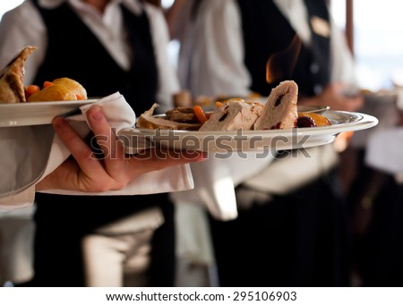 Waiters carrying plates with meat dish at a wedding - stock photo