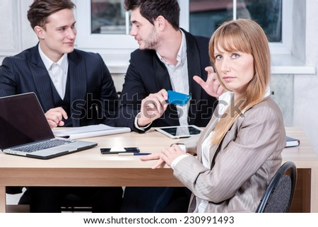 Waiting for a breakthrough. Businesswoman sitting at table and looking away while her colleagues businessmen talking in the background sitting at table - stock photo