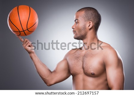 Waiting for a game. Side view of young shirtless African man carrying basketball ball on finger while standing against grey background - stock photo