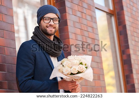Waiting for her. Handsome young man in smart casual wear holding bouquet of flowers and smiling while standing at the street  - stock photo