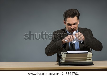 Waiting for idea. Handsome excited young author working at the typewriter and tearing paper while sitting at his working place against grey background - stock photo