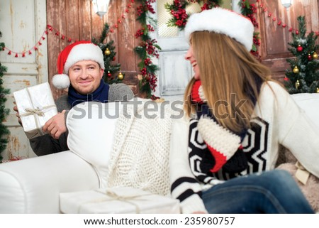 Waiting for ideal Christmas. Young and beautiful pair is in festive New Year living room Man is ready to give Christmas present to his beautiful wife. Girl is sitting on the sofa  - stock photo