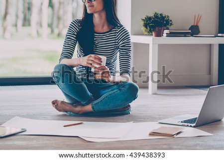 Waiting for inspiration. Close-up of confident young beautiful woman holding coffee cup and smiling while sitting on the floor at home with blueprint laying near her  - stock photo