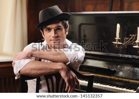 Waiting for inspiration. Portrait of handsome young men sitting in front of his piano - stock photo