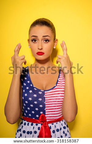 Waiting for special moment. Cheerful young caucasian woman keeping fingers crossed while standing against yellow background. Concept of wishing or praying about something - stock photo