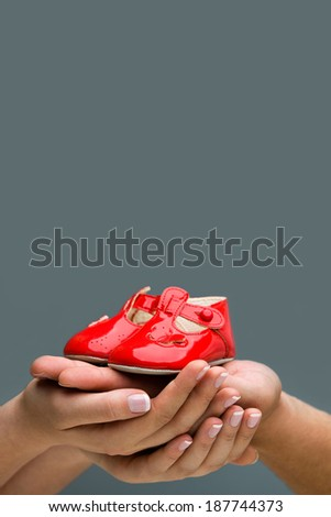 Waiting for the birth. Parents Expecting a baby. Woman and her husband holding baby shoes in their hands. Background with copyspace.  - stock photo