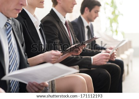 Waiting in line. Cropped image of people in formalwear waiting in line while sitting at the chairs and holding papers in their hands - stock photo
