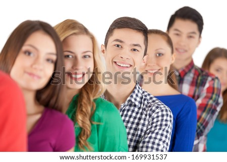 Waiting in line. Young people standing in a row and smiling at camera while isolated on white - stock photo