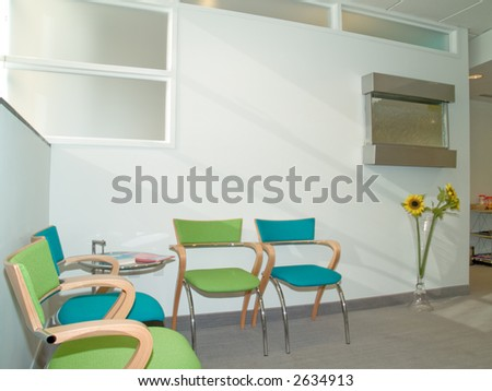 Waiting room with blue and green chairs - stock photo