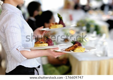Waitress carrying three plates with meat dish - stock photo
