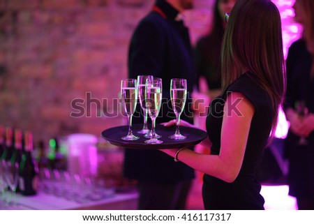 Waitress holding a dish with champagne glasses - stock photo