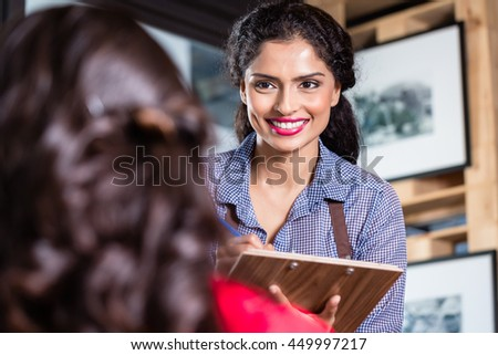 Waitress in indian restaurant or cafe taking orders, close - stock photo