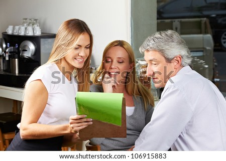 Waitress offering the menu to senior couple and making a recommendation - stock photo