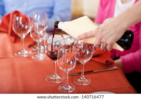 waitress pouring red wine at guest�´s glasses - stock photo