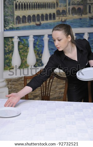 waitress puts the dishes in restaurant - stock photo