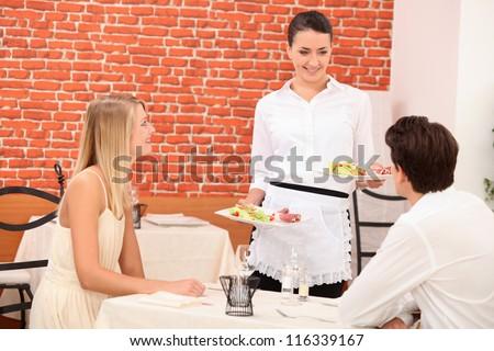 Waitress serving couple - stock photo