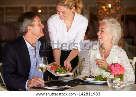Waitress Serving Food To Senior Couple In Restaurant - stock photo