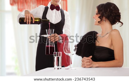 Waitress serving wine to a smiling lady guest. Isolated with work path - stock photo