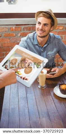 Waitress taking handsome hipsters order with tablet against food app - stock photo