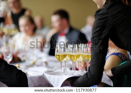 Waitress with dish of champagne and wine glasses - stock photo