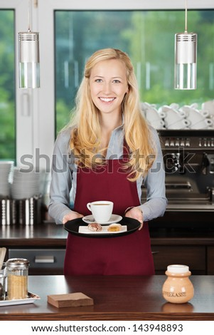 waitress with red apron holding a cup of coffee - stock photo