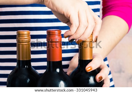 Waitress woman opens a bottle of red wine - stock photo