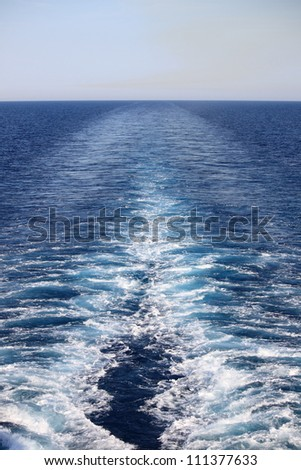 Wake of a cruise ship on the open ocean - stock photo