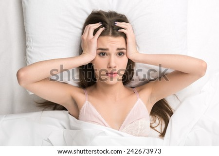 Wake up already. Beautiful young woman touching her head struggling to wake up while lying on the bed  - stock photo