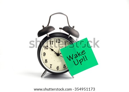 Wake up call concept with alarm clock and green adhesive note - stock photo