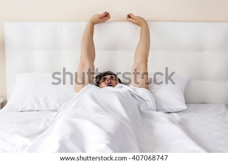 Wake up concept. Man stretching in a bed. - stock photo