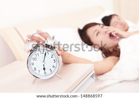 Wake up - Tired couple touch the alarm clock while they are sleeping in bed, asian family - stock photo